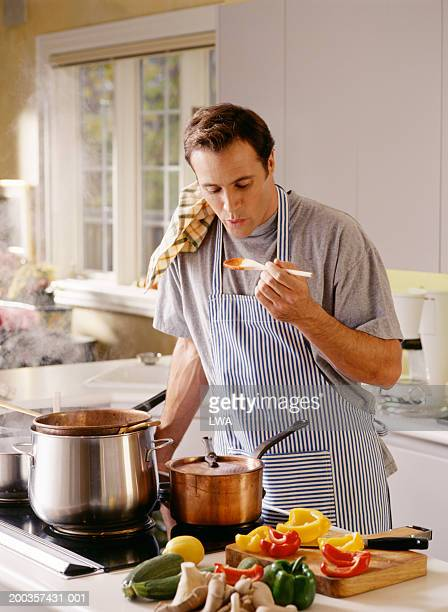 Man cooking, blowing on sauce