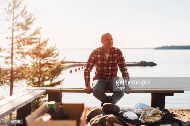 cuisson d'homme par une poursuite de plein air de feu de camp - vie simple photos et images de collection