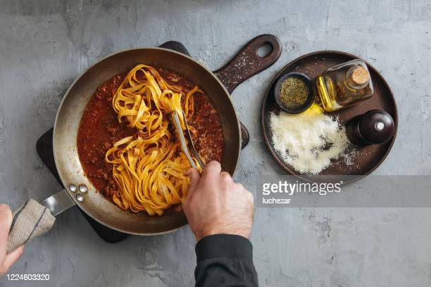 man cooking classic tagliatelle with sauce bolognese - italian culture stock pictures, royalty-free photos & images