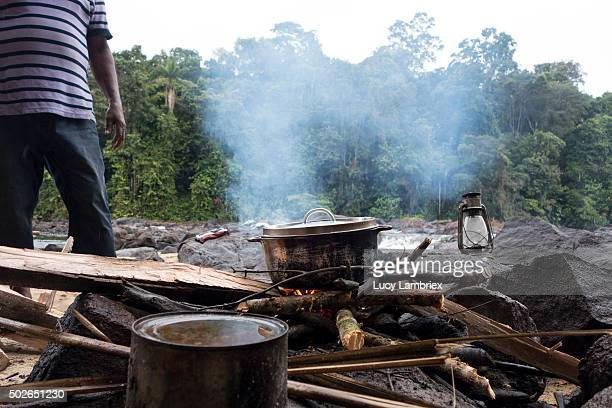 Man cooking dinner on logfire at Suriname river