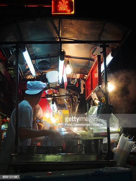 man cooking food at stall - one night stand stock-fotos und bilder