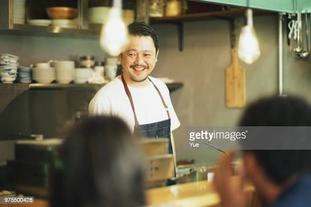 man cooking in a kitchen at japanese pub - catering building stock pictures, royalty-free photos & images