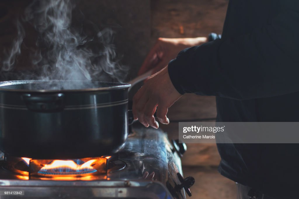 A man cooking in a rustic cabin : Stock Photo