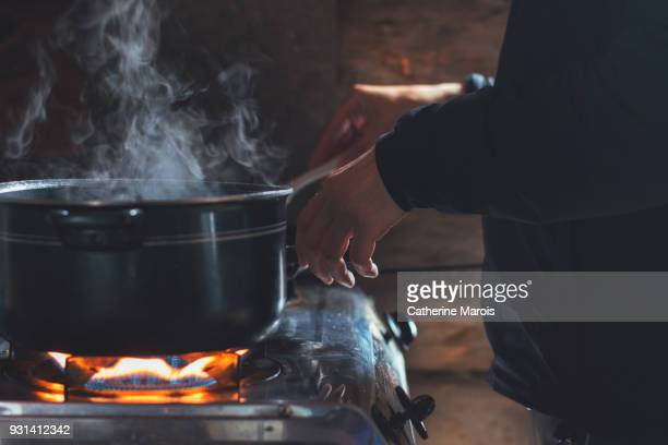 A man cooking in a rustic cabin