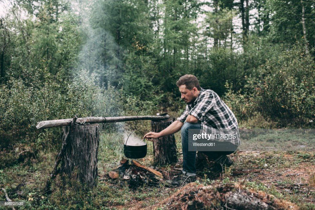 Man cooking in cauldron in rural landscape : Stock-Foto