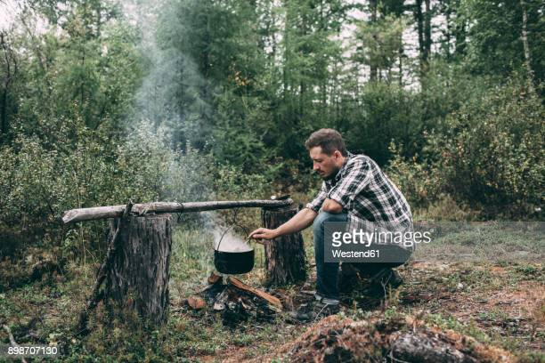 man cooking in cauldron in rural landscape - survival stock pictures, royalty-free photos & images
