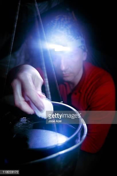 A man cooking in his tent by the light of his headlamp while camping on Mt. Washington.