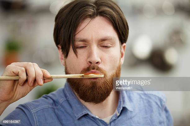 Man cooking in kitchen tasting from wooden spoon