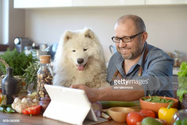 man cooking in the kitchen ( with Samoyed Dog)