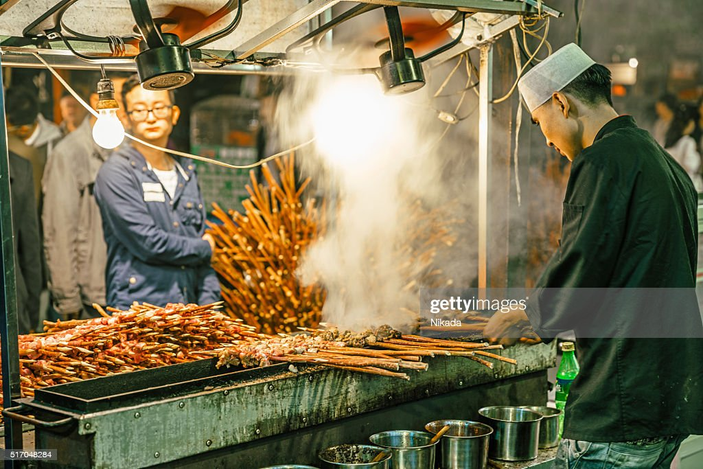 man cooking meat, muslim street market in Xi'an, China : Stock Photo