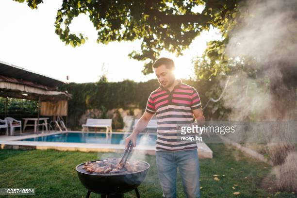 man cooking meat on bbq - grilling stock pictures, royalty-free photos & images
