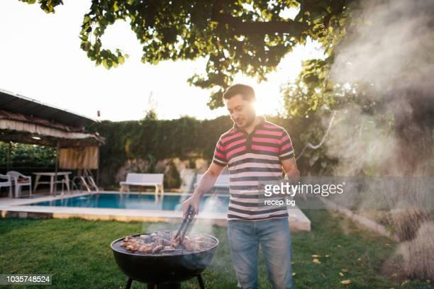 mann kochen fleisch am grill - ein mann allein stock-fotos und bilder