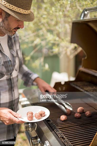 Man cooking meatballs on a BBQ outside garden