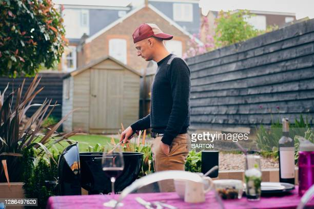 man cooking on barbecue in back garden - one mid adult man only stock pictures, royalty-free photos & images