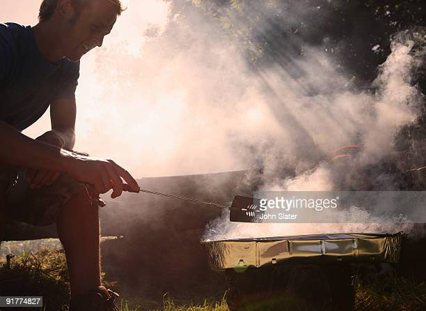 man cooking on BBQ at campsite