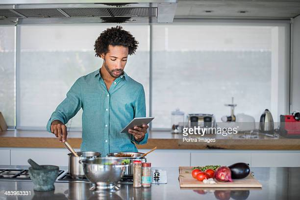 Man cooking reading a tablet while cooking