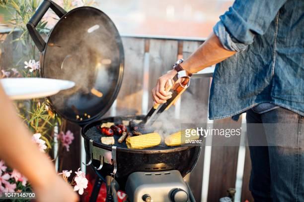 mann kochen würstchen auf grill - grillen stock-fotos und bilder