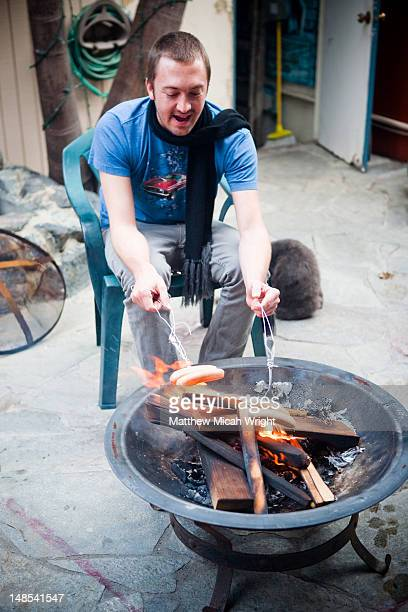 man cooking sausages on makeshift barbeque. - makeshift stock pictures, royalty-free photos & images