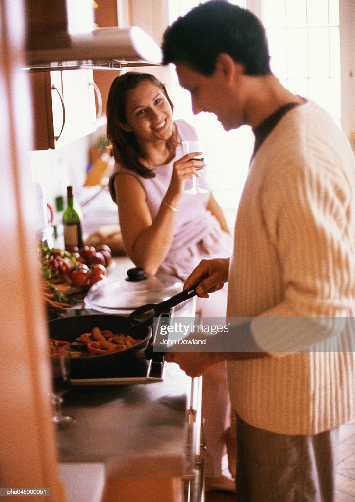 Man cooking, side view, woman holding glass, smiling : Stock Photo
