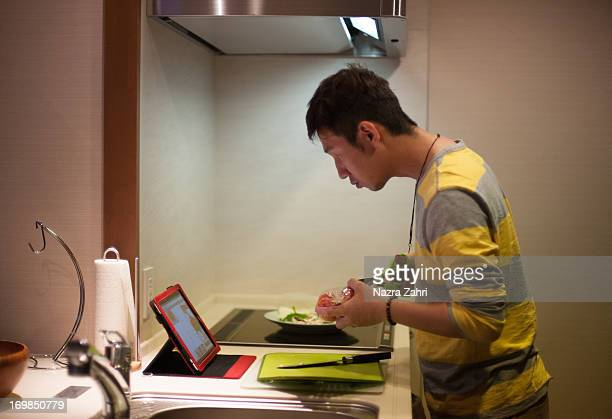 Man cooking while looking at recipe on tablet pc