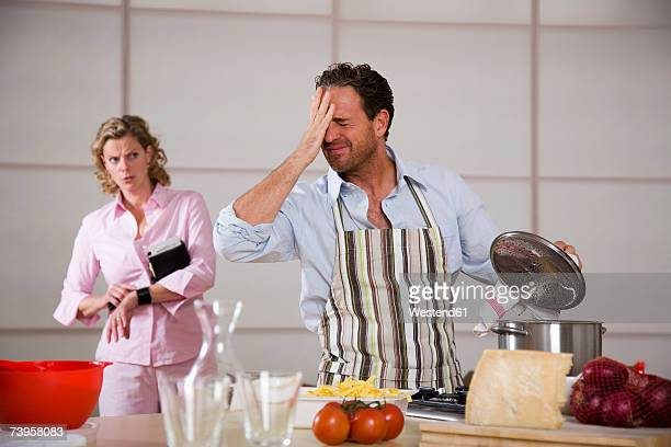 Man cooking, woman standing in background