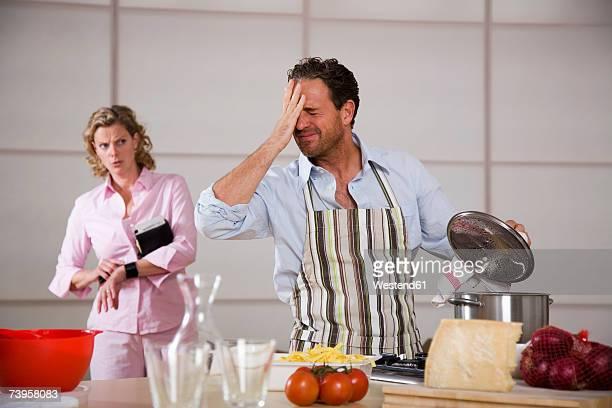 man cooking, woman standing in background - manos a la cabeza fotografías e imágenes de stock