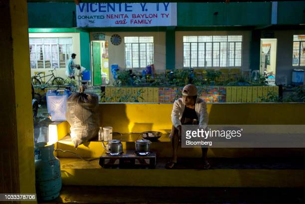 A man cooks a meal at a temporary evacuation center at Balzain East Elementary School ahead of Typhoon Mangkhut's arrival in Tuguegarao Cagayan...