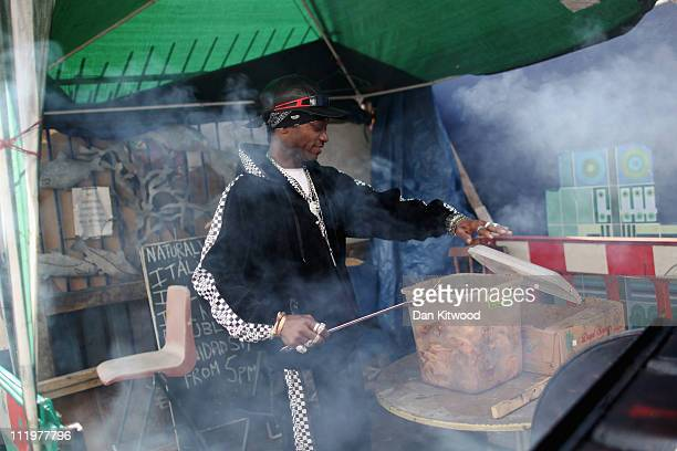 A man cooks chicken on a barbeque in Brixton on April 11 2011 in London England Today marks the 30th anniversary of the Brixton riots The 1981...