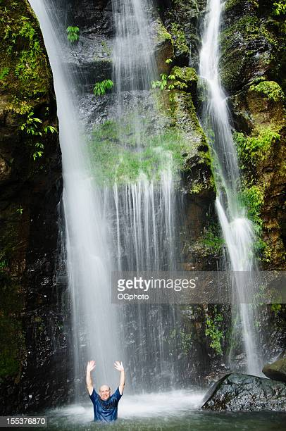 Man cooling down in a waterfall