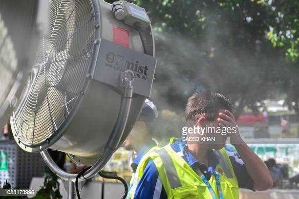 A man cools down in front of a mist fan for relief from the hot weather on day 12 of the Australian Open tennis tournament in Melbourne on January 25...