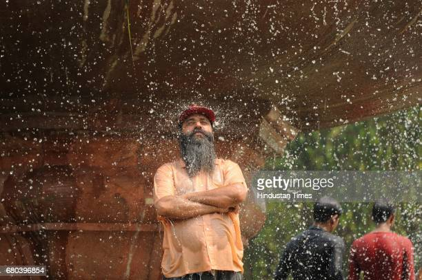 A man cools off at a fountain near India Gate lawns during a hot day on May 8 2017 in New Delhi India Temperature in Delhi/NCR soared to a maximum of...