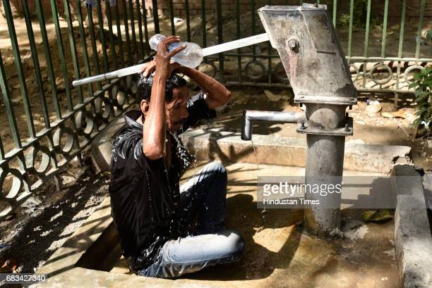 A man cools off on a roadside hand pump on a hot summer day on May 15 2017 in New Delhi India Heat wave conditions prevailed in the capital as...