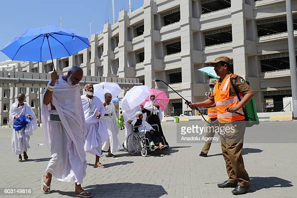 A man cools the prospective pilgrims as they on their way to Jamarat to stone the devil as part of the annual Islamic Hajj pilgrimage during the Eid...