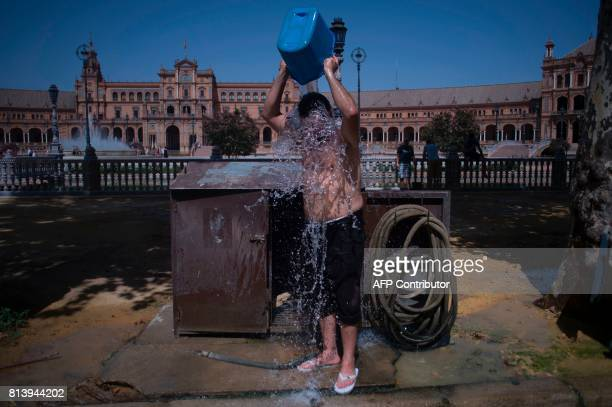 A man cools with a bucket of water next to Plaza de Espana in Sevilla during a heat wave on July 13 2017 / AFP PHOTO / JORGE GUERRERO