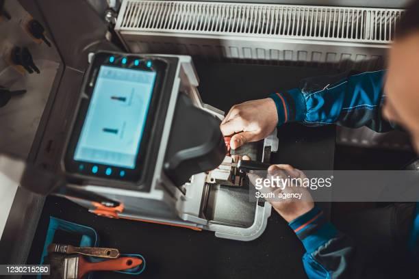 mens die autosleutel met sleutelkopiemachine kopieert - locksmith stockfoto's en -beelden