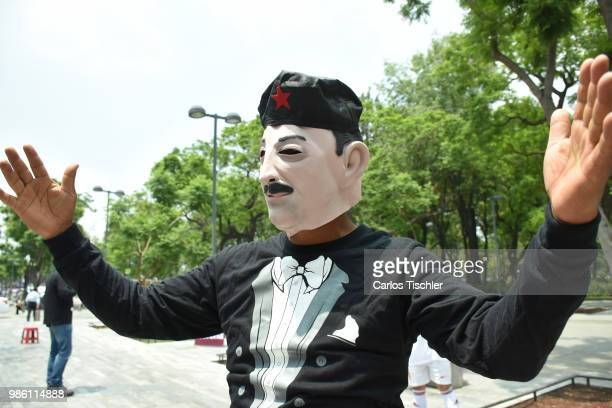 A man costumed as Carlos Salinas de Gortari of The Mafia of Power team and integrants of Morena Political party offers a match at Alameda Central on...