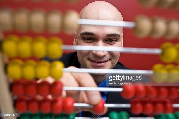Hombre contando colorido encapsulados en una calculadora de China.