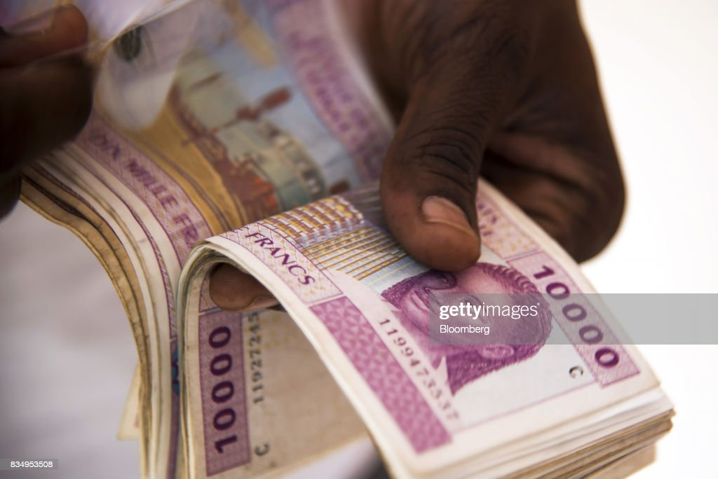 A man counts 10,000 denomination Central African franc banknotes in this arranged photograph in N'Djamena, Chad, on Wednesday, Aug. 16, 2017. African Development Bank and nations signed agreement to finance a project linking the town of Ngouandere in Cameroon and Chads capital, NDjamena, according to statement handed to reporters in Cameroonian capital, Yaounde in July. Photographer: Xaume Olleros/Bloomberg via Getty Images