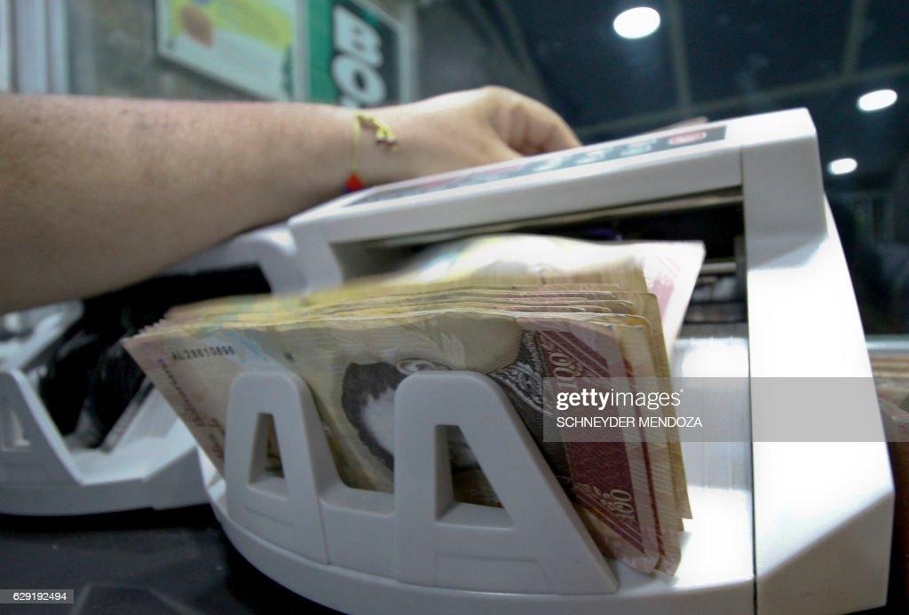 A man counts bolivar bills on a machine at a bureau de change