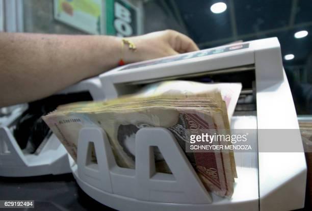 Man counts 100-bolivar-bills on a machine at a bureau de change in La Parada, municipality of Villa del Rosario, Norte de Santander department,...
