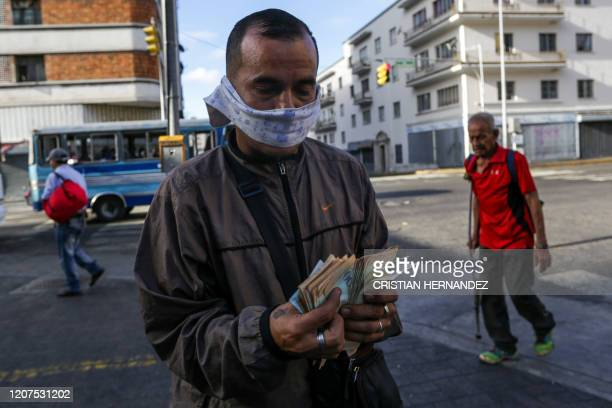 Man counts bills wearin a makeshift face mask as a precautionary measure against the spread of the new coronavirus, COVID-19, in Caracas, on March...