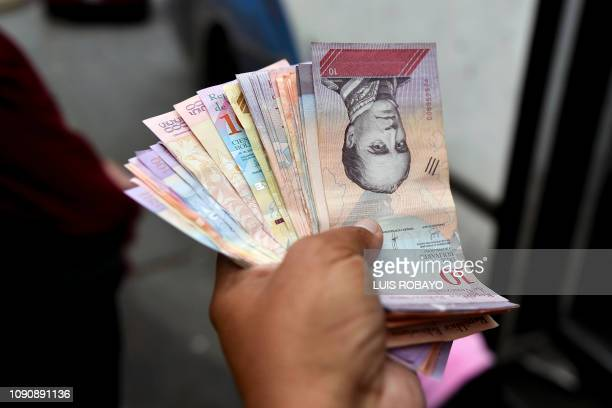 Man counts Bolivar bills in a street of Caracas on January 29, 2019. - Venezuela devalued its currency by almost 35 percent on Monday to bring it...
