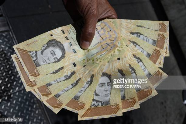 Man counts bolivar bills in a street of Caracas on March 18, 2019. - Production cutbacks by OPEC nations are building a supply cushion that could be...