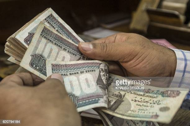 A man counts Egyptian pounds at currency exchange shop in downtown Cairo on November 3 2016 Egypt floated the country's pound as part of a raft of...