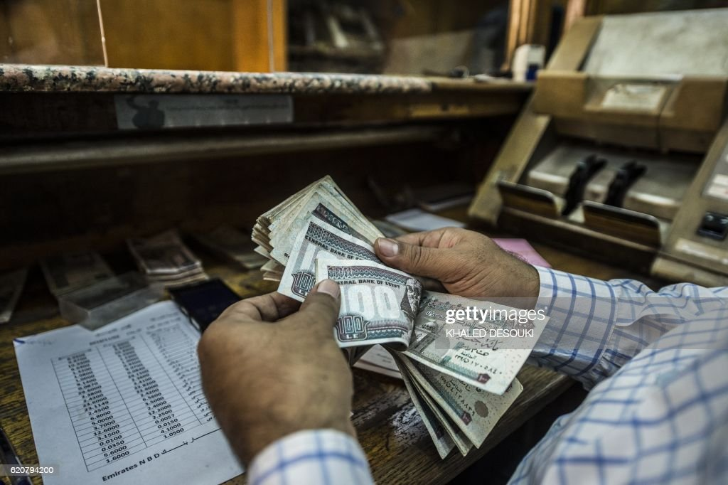 A man counts Egyptian pounds at currency exchange shop in downtown Cairo on November 3, 2016. Egypt floated the country's pound as part of a raft of reforms, after a dollar crunch and exorbitant black market trade threatened to grind some imports to a halt. / AFP / KHALED