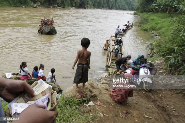 A man counts his money after assisting motorcyclists to cross Cisadane River in Rumpin Bogor West Java Indonesia on March 13 2018 The bridge linking...