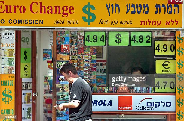 A man counts his money after exchanging US dollars at a money changer September 25 2002 in Tel Aviv Israel The buy and sell rates are prominently...