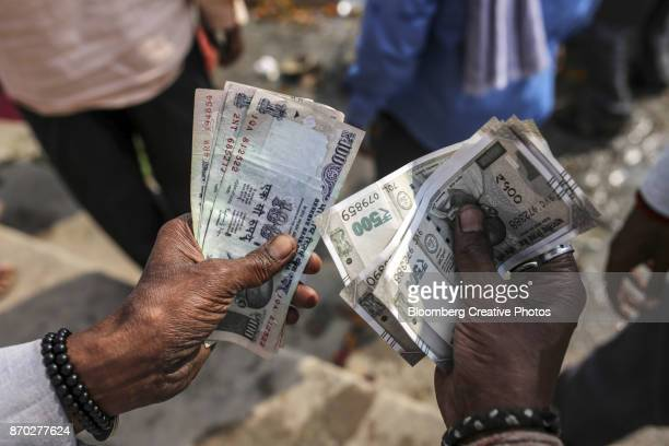a man counts indian rupee banknotes - indian currency stock photos and pictures