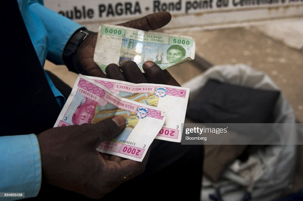 A man counts out Central African franc banknotes on a street in N'Djamena, Chad, on Wednesday, Aug. 16, 2017. African Development Bank and nations signed agreement to finance a project linking the town of Ngouandere in Cameroon and Chads capital, NDjamena, according to statement handed to reporters in Cameroonian capital, Yaounde in July. Photographer: Xaume Olleros/Bloomberg via Getty Images