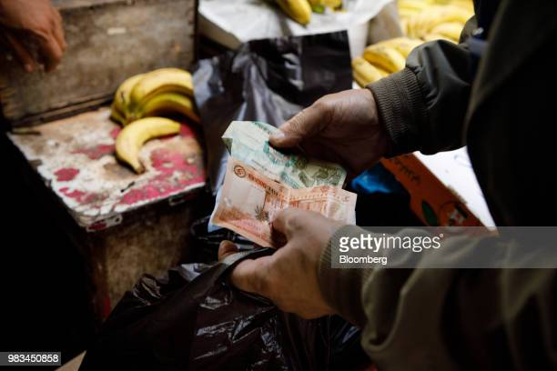A man counts out Jordanian dinar banknotes at a local fruit and vegetable market in Amman Jordan on Thursday June 21 2018 President Trump and First...